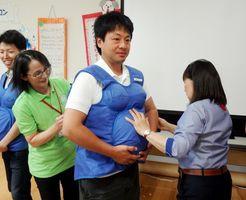 妊婦エプロンを装着する参加者=佐賀市の子育て支援センター「ゆめ・ぽけっと」