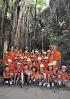 沖縄のガンガラーの谷でガジュマルの木をバックに記念撮影する参加者たち(昨年の活動の様子、提供写真)