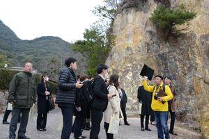 ガイドの案内で泉山磁石場を見学する旅行会社の修学旅行担当者=有田町