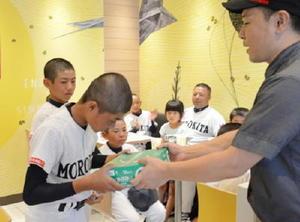 森本博文店長から野球ボールを受け取る選手=佐賀市のマクドナルド佐賀南バイパス店