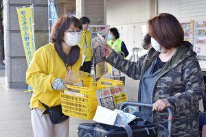 買い物客にチラシやグッズを配って人権への配慮を呼び掛ける関係者=佐賀市兵庫北のゆめタウン佐賀