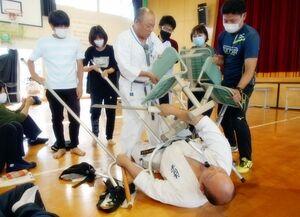 椅子やさすまたなどを使った不審者対応を学ぶ職員ら=佐賀市の大和特別支援学校(提供写真)