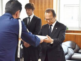 白仁田浩司署長(左)から指定書を受け取る事業所の代表者=佐賀市の佐賀南署