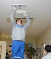 照明を磨き上げる九電工の従業員=佐賀市東与賀町の「めぐみ園」