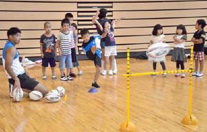 ゴールキックを体験する子どもたち。ゴールが決まると、体全体で喜びを表現していた=みやき町コミュニティーセンターこすもす館