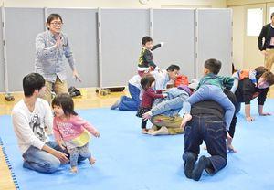 体を使った遊びを通し、ふれあう参加の父親と子ども=神埼市の千代田町保健センター