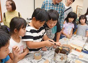 和紙などで作った芯に溶けた蝋をかける子どもたち=みやき町の鳥栖・三養基西部リサイクルプラザ