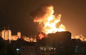 13日、パレスチナ自治区ガザで、空爆を受けて立ち上る煙と炎(ゲッティ=共同)