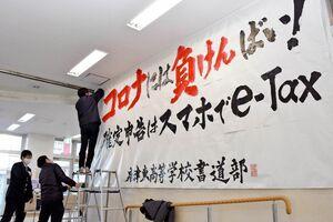 唐津東高書道部の作品を設置する唐津税務署の職員=唐津市南城内の大手口バスセンター