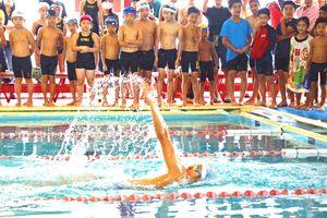 子どもたちが見守る中、背泳ぎを披露する金持義和さん=伊万里スイミングクラブ