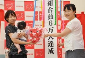 組合員6万人目となった農﨑亜美さん(左)家族に記念品を手渡す桑原廣子会長=佐賀市のコープさが新栄店