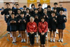 三重津かるたを贈呈した副田峰子部会長(中央左)らと中川副小学校の6年生=佐賀市川副町の中川副小学校