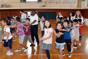 児童と一緒に「電車遊び」を楽しむ短期留学中の米国の高校生=小城市の桜岡小学校