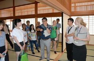 建築構造などの説明を熱心に聞く留学生ら=佐賀市城内の佐賀城本丸歴史館