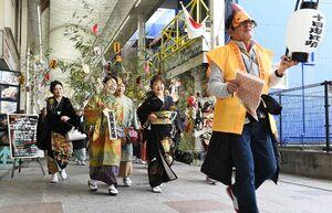 商売繁盛を願い、ササを手に商店街を練り歩く着物姿の女性たち=佐賀市白山
