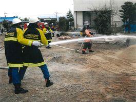 防火訓練で放水の実演をする消防団員