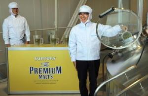 「仕込み再開式」でホップを煮沸釜に入れるサントリービールの水谷徹社長(右)=8日、熊本県嘉島町