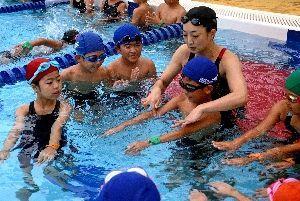 子どもたちの手を取りながら水のかき方などを丁寧に教える岩崎恭子さん=白石町の有明スカイパークふれあい郷
