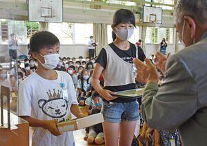 全校での登校時のごみ拾いが評価され、代表で表彰状を受け取った6年生=唐津市の長松小