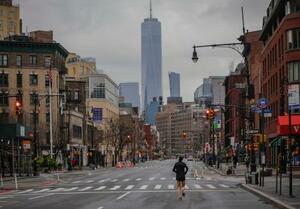 28日、米ニューヨークで、人影が消えた街中をジョギングする市民(AP=共同)