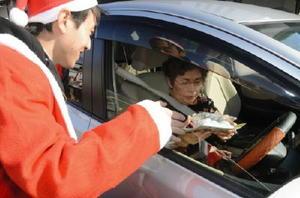 ドライバーに三色餅を手渡し、交通安全を呼び掛けるJAさが白石地区の職員(左)=白石町