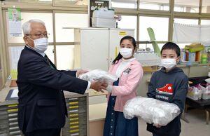 吉田教育長(左)からマスクを受け取る児童=江北小