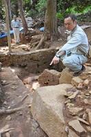 徳川家康陣跡の南東側虎口の発掘現場。学芸員2人の足元に虎口両端の礎石があり、手前の学芸員が指さす角石はノミで面が整えられている=唐津市鎮西町