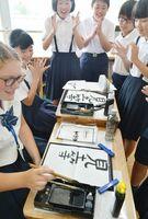 児童に当てはめてもらった漢字で、自分の名前を書くケンドラ・プレスコットさん(左)=佐賀市の金立小