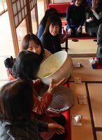 隣の人の手を借りながら巨大な茶碗でお茶を味わう参加者たち=唐津市鎮西町の茶苑海月