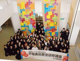 ミヤザキケンスケさんのワークショップを通じ、テトリスを模した巨大な作品を完成させた日韓の中高生たち=佐賀市の佐賀北高
