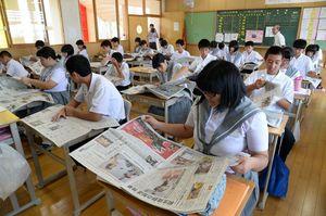 出前授業で各自新聞をめくり、興味のある記事を読む生徒=小城市の小城中