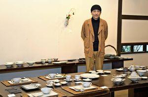 吉田求さんと、吉田さんがデザイン性を追求したカップや皿などの食器=佐賀市の高伝寺前村岡屋ギャラリー