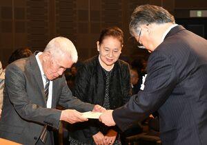 佐賀新聞社の坂田勝次常務取締役(右)から表彰状を受ける夫婦=佐賀市のアバンセ