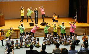 ティーンズミュージカルSAGA、ふたばこども園の子どもたちと「にゃんこパトロール」を披露したカノエラナさん(ステージ中央)=佐賀市のメートプラザ佐賀