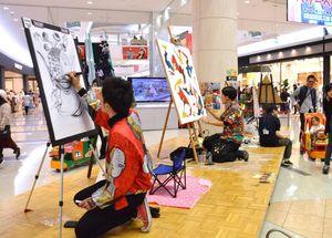 「冨永ボンドのファミリア展」のライブペイントで、作品を仕上げていくアーティストたち=佐賀市のゆめタウン佐賀・セントラルコート