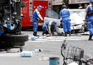歩行者が巻き込まれた交通事故の現場を調べる警察官=19日午後1時38分、東京都豊島区