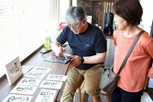 来店者の依頼で筆文字アートを制作する「カスタネット」の中村碩亨社長=みやき町の「お菓子のじろう」