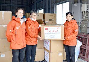 「日本加油!(日本頑張れ)」と書かれた支援物資を手に笑顔を見せるアジアパシフィックアライアンス・ジャパンのスタッフ=佐賀市の佐賀空港