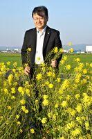 仕事帰りに、菜の花ロードを訪れた杉野直志さん。後方は鳥栖市街地=同市安楽寺町