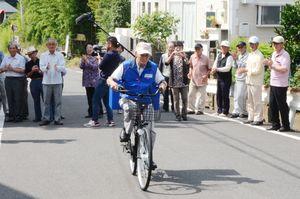 住民の拍手の中、宅配代行第1便を載せた自転車で出発する柴原信喜さん=伊万里市大坪町