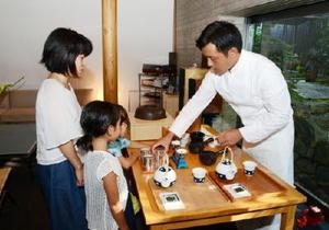 秤や砂時計を使い細部までこだわった実演で茶を入れてみせる「嬉野茶寮」のスタッフ(右)=嬉野市の和多屋別荘