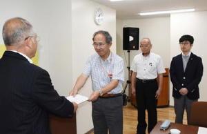 秀島市長(左)に答申書を手渡す荒牧委員長=佐賀市役所