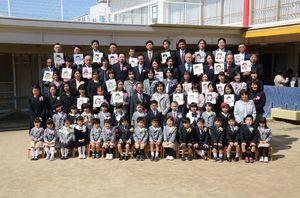 卒園式の記念撮影では、保護者が子どもの似顔絵を手に並んだ=佐賀市の日新こども園