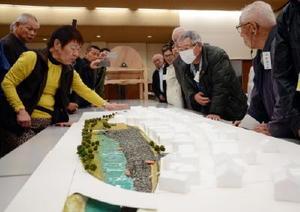 九州大大学院の林博徳助教らが制作した塩田津の模型を参考にしながら塩田津の未来を話し合う参加者たち=嬉野市の塩田公民館