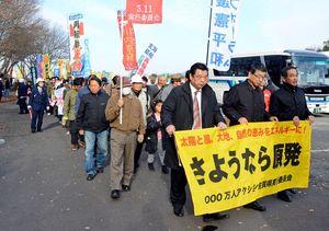再稼働反対ののぼりや横断幕を掲げてデモ行進する参加者=唐津市鏡の河畔公園