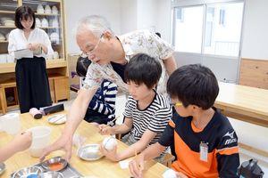 松尾嘉之さんの指導を受け風鈴に絵付けをする児童=有田町の有田小