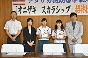 金丸美智夫会長(右)から招待状を受け取った大倉樹乃さん(右から3人目)と原田彩心さん(同2人目)=多久市役所