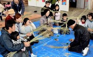 地元農家の指導を受けながらリース状のしめ縄をつくる参加者=有田町役場