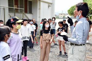 東原庠舎東部校の5年生に旬のビワを届けた田渕厚さん(右)=多久市の同校