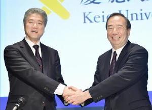 記者会見の冒頭、握手する慶応大文学部教授の長谷山彰氏(左)と清家篤塾長=20日午後、東京都港区